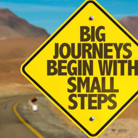 "Sign post saying ""Big Journeys Begin With Small Steps"""